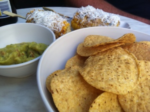 An image of barbequed corn, tortilla chips and guacamole