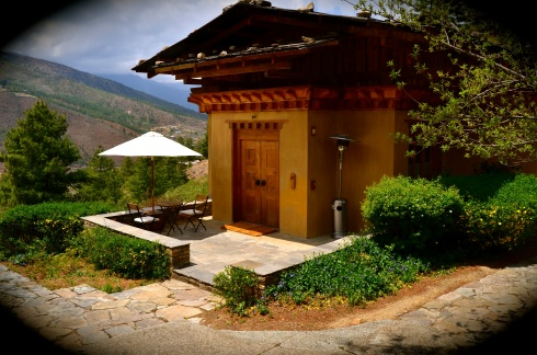 the villa at Uma Paro with traditional wooden roof and outdoor table with umbrella