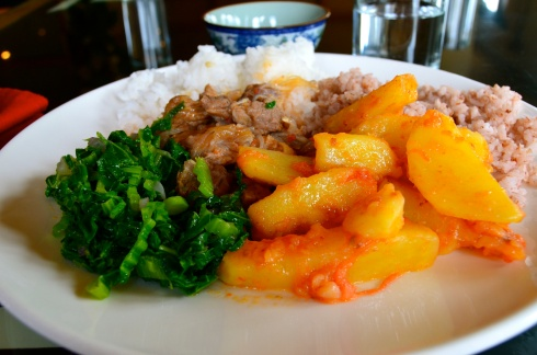 A typical Bhutanese meal of potatoes, red rice, morning glory and a meat stew