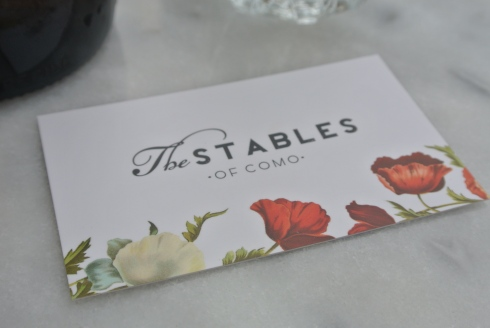 A business card of The Stables