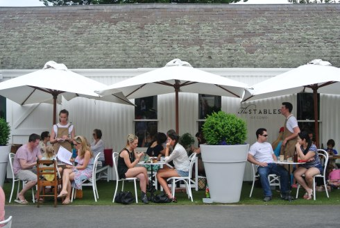 Tables and umbrellas outside the Stables at Como House