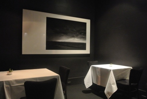 Attica's dining room with black glossy walls, heavy white tablecloths and dramatic black and white photographs of landscapes